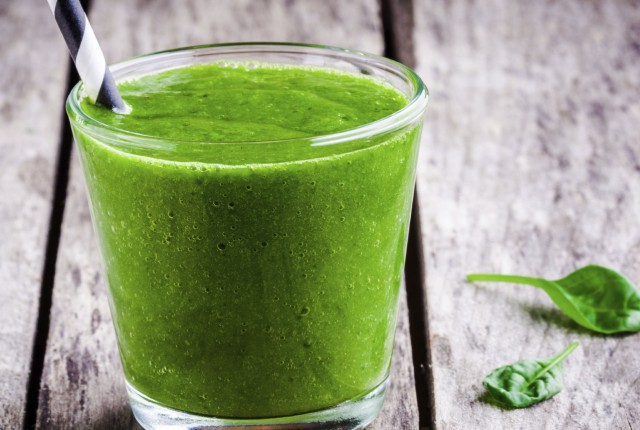 Healthy green spinach smoothie on wooden rustic table